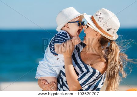 A young mother and her delightful little son on vacation at the beach.