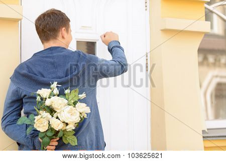 Pleasant guy holding flowers