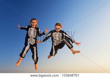 Young Girls In Halloween Costumes Jump High With Fun