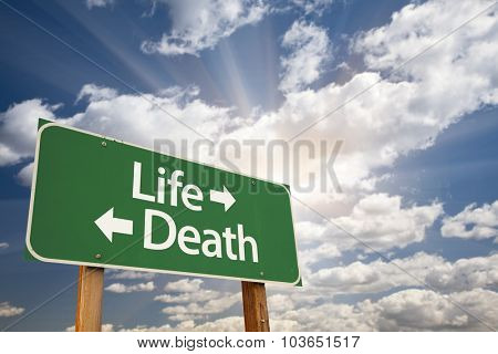 Life and Death Green Road Sign With Dramatic Clouds and Sky.