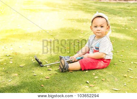Asian Baby Taking Selfie Photo On The Green Grass Field In The Park