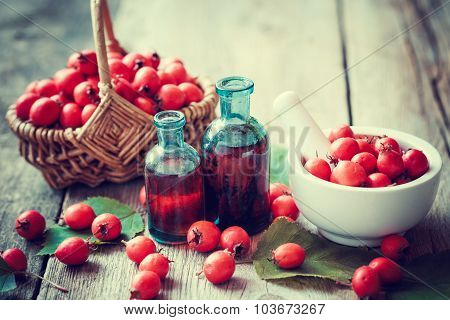 Mortar Of  Hawthorn Berries, Two Tincture Bottles And Thorn Apples In Basket On Rustic Table. Herbal