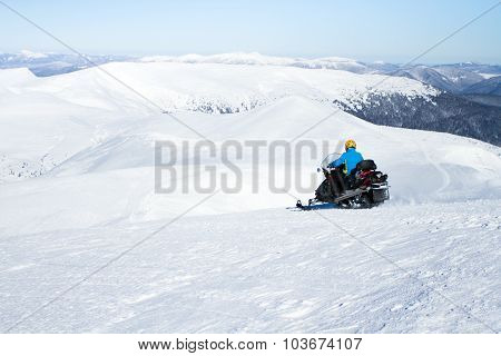 Man on snowmobile in winter mountain.