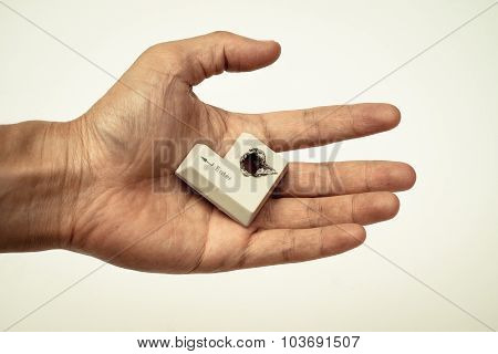 Hacker's hand picking up computer enter button with a hole representing computer security breach