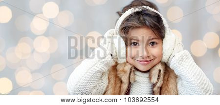 winter, people, christmas happiness concept - happy little girl wearing earmuffs and gloves over holidays lights background