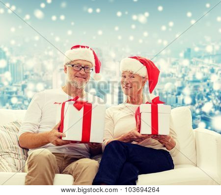 family, holidays, christmas, age and people concept - happy senior couple in santa helper hats with gift boxes over snowy city background