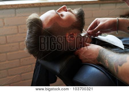 barber shaving man with vintage straight razor in barbershop