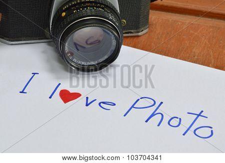 Model of Pentax K 1000 film camera on paper write I love pho