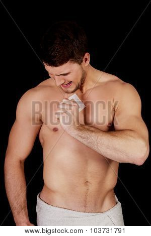 Handsome muscular man waxing his chest. poster