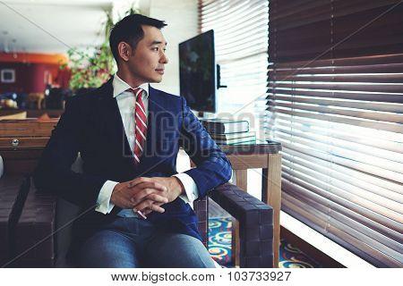 Intelligent men entrepreneur in elegant suit thinking about something before meeting