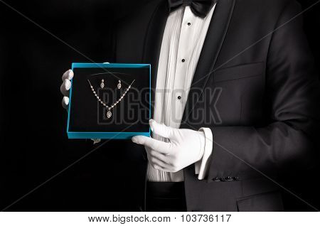 Elegant man in tuxedo presenting jewelery - isolated on black poster