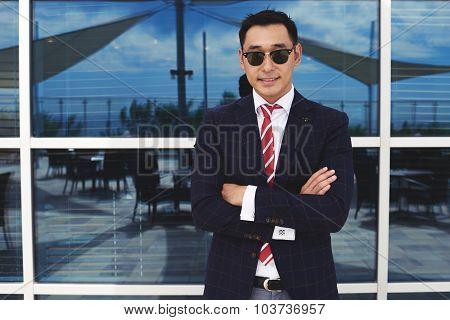 Happy successful men entrepreneur in formal wear posing against office building