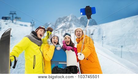 winter sport, leisure, friendship, technology and people concept - happy friends with snowboards and taking picture by smartphone on selfie stick over downhill skiing and mountains background