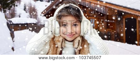 winter holidays, season, christmas, people and children concept - happy little girl wearing earmuffs and gloves over wooden country house background and snow