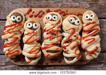 Halloween homemade food sausage meatball mummies wrapped in dough, baked and covered with fake blood