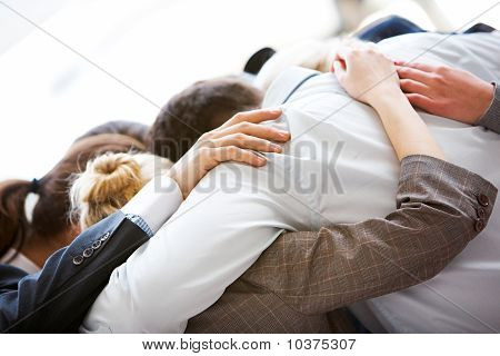 Circle of business people embracing each other with their heads bowed while concentrating poster