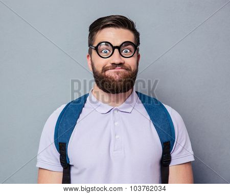 Portrait of a male nerd with funny face over gray background