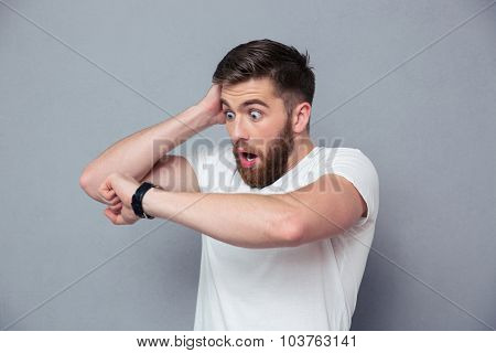 Portrait of a shocked man looking on wrist watch over gray background