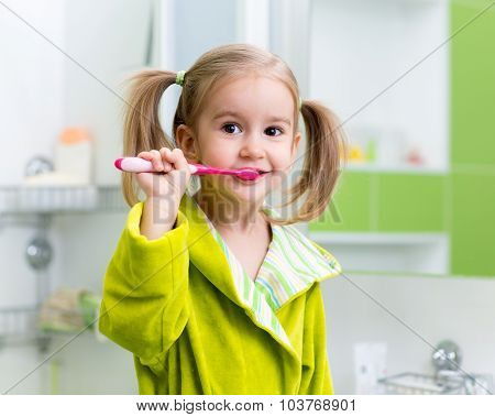 Little girl brushing teeth in bath