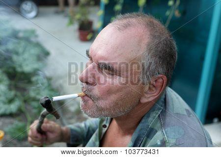 Man Lights A Cigarette