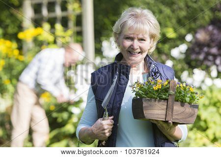 Portrait Of Senior Couple Working In Garden Together