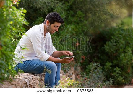 young latin man searching internet coverage outdoor