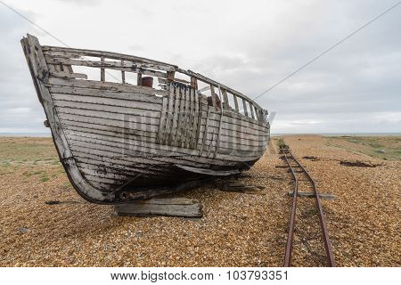Side Of Old Derelict Boat With Rails On Pebble Beach.