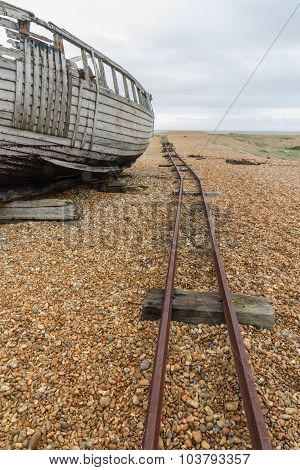 Old Derelict Boat With Rails On Pebble Beach.