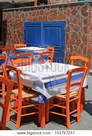 Greek Tavern With Orange Wooden Chairs By The Sea Coast, Greece, Santorini Island In Cyclades