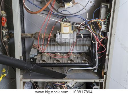 Repairman Vacuuming Inside Of A Gas Furnace