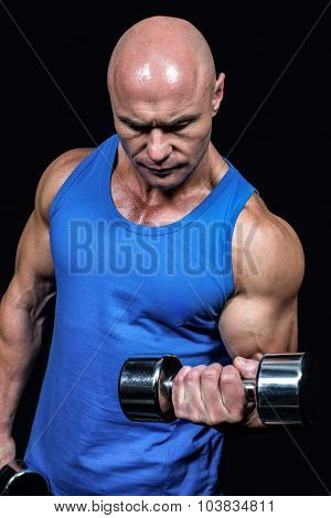 Bald man in blue vest lifting dumbbells against black background