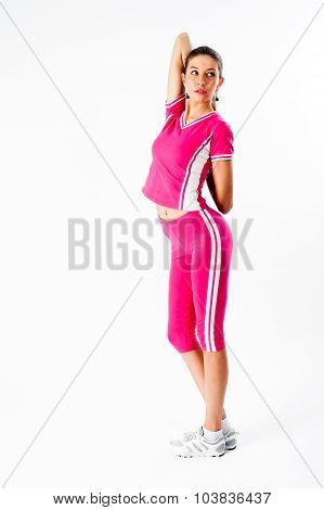 Attractive fit woman in pink sportsuit warms up