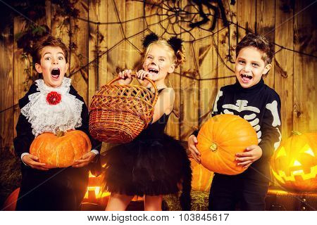 Group of joyful children in halloween costumes posing together in a wooden barn with pumpkins. Halloween concept. poster