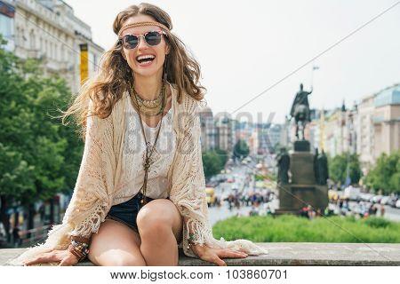 Hippy-looking Woman Tourist Sitting On Stone Parapet In Prague