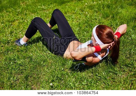 Fit girl lying on grass and doing situps
