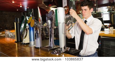 Barkeeper holding glass standing in front of beer dispenser at bar