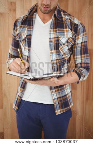 Mid section of businesman writing with pencil on diary against wooden wall