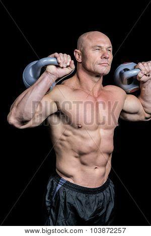 Bodybuilder lifting kettlebells against black background poster