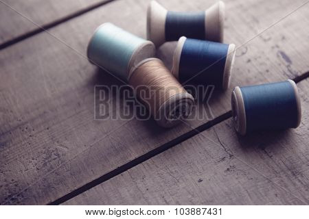 Old sewing thread wooden reels or bobbins on a old rustic work bench. Intentionally shot in muted retro-vintage tone and shallow depth of field. (soft focus)