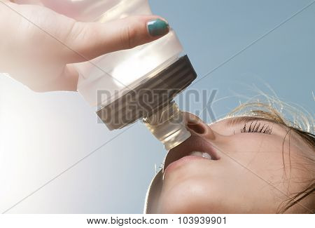 Young sporty woman drinking water from a bottle against the blue