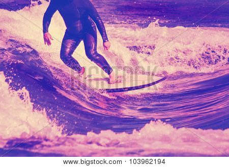 surfer riding a wave in a full wet suit toned with a retro vintage instagram filter app or action effect
