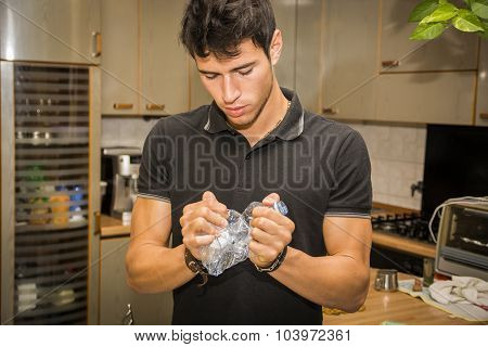 Young Man Crushing Plastic Water Bottle in Kitchen