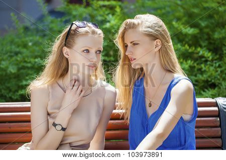 Close up portrait of Two young beautiful women secret at summer green park