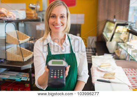 Portrait of happy female shop owner holding credit card reader in bakery