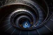 Long spiral, winding stairs. Dark shadows, mysterious mood with single soft light. poster
