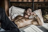 Shirtless sexy male model lying alone on his bed in his bedroom, looking away with a seductive attitude poster