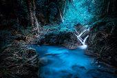 Mystery night at deep tropical rain forest with flowing cascade waterfall. Fantasy jangle landscape. Erawan National Park Kanchanaburi Thailand poster