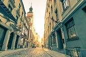 Vintage retro travel postcard of a narrow medieval street in old town Riga at sunset with sun reflection - Latvia - European capital of culture 2014 poster
