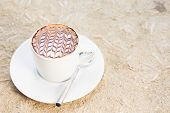 Overhead view of cafe latte with topping on it. Standing on sand. Horizontal poster