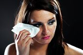 Hurt woman crying face with smeared make up on dark background poster
